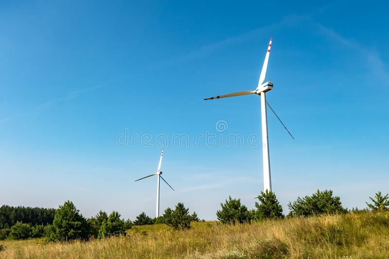 Rotating blades of a windmill propeller on blue sky background. Wind power generation. Pure green energy.  stock image