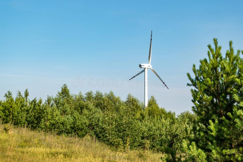 Rotating blades of a windmill propeller on blue sky background. Wind power generation. Pure green energy.  stock images