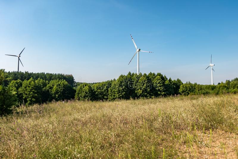 Rotating blades of a windmill propeller on blue sky background. Wind power generation. Pure green energy.  royalty free stock image