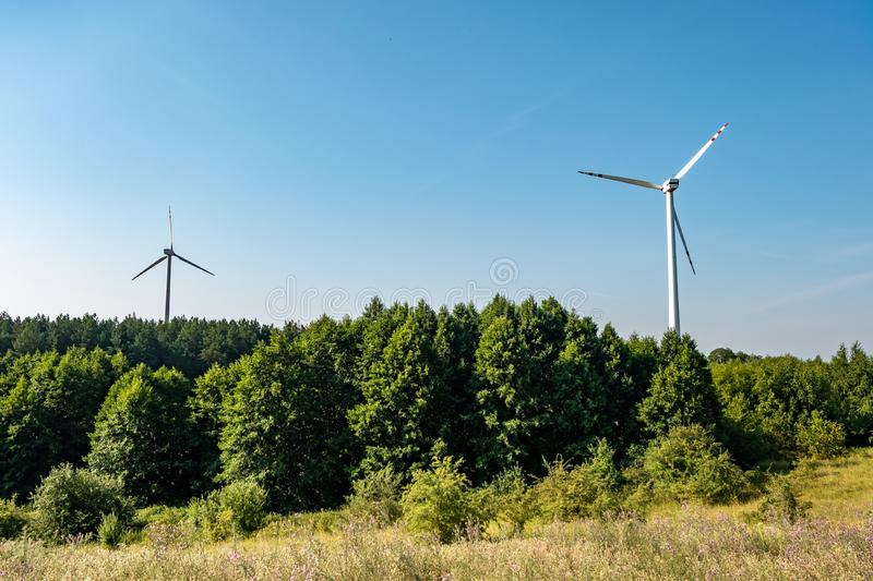 Rotating blades of a windmill propeller on blue sky background. Wind power generation. Pure green energy.  stock photos