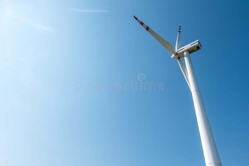 Rotating blades of a windmill propeller on blue sky background. Wind power generation. Pure green energy.  stock photo
