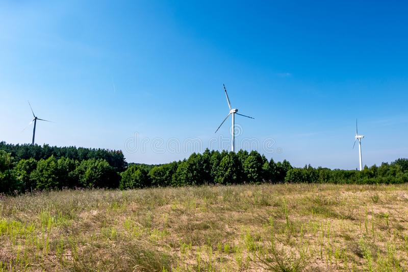 Rotating blades of a windmill propeller on blue sky background. Wind power generation. Pure green energy.  royalty free stock images