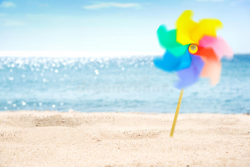 Rotating colorful pinwheel on the beach background. stock photo