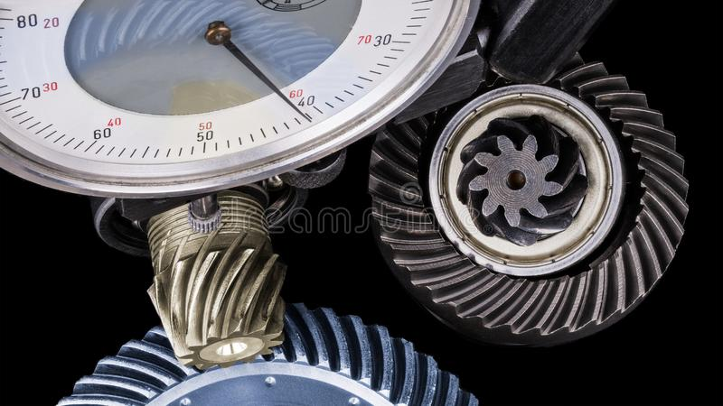 Close-up of gear measurement with indicator. Rotating interlocked cogwheels on a black background. Idea of accuracy, quality control, teamwork and engineering royalty free stock images