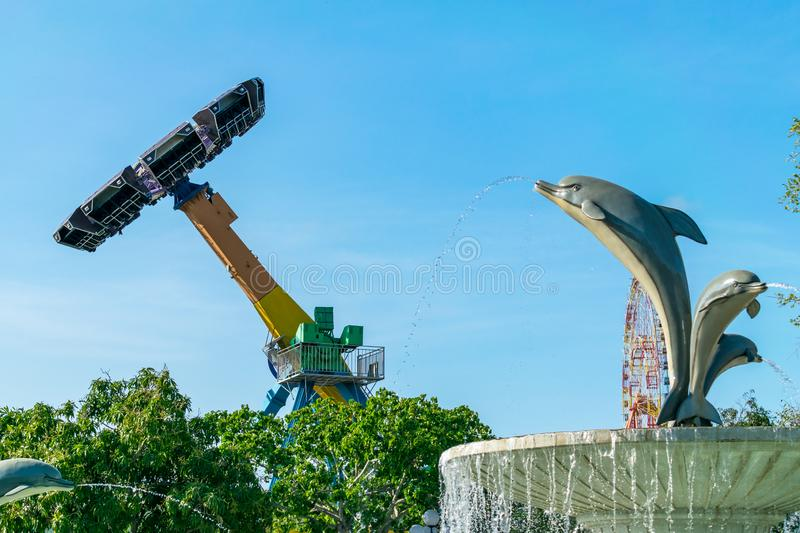 Rotating merry-go-round in the sky with a dolphin-shaped fountain in amusement park royalty free stock images