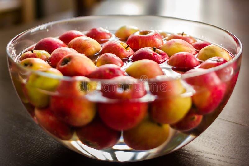 Rote Äpfel, die ein Bad in der Glasschüsselfülle mit Wasser nehmen stockfotografie