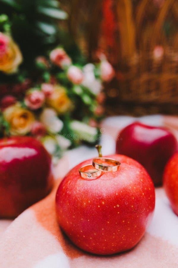 Rote Äpfel und Eheringe auf einer Plaiddecke nahe dem Korb lizenzfreies stockbild