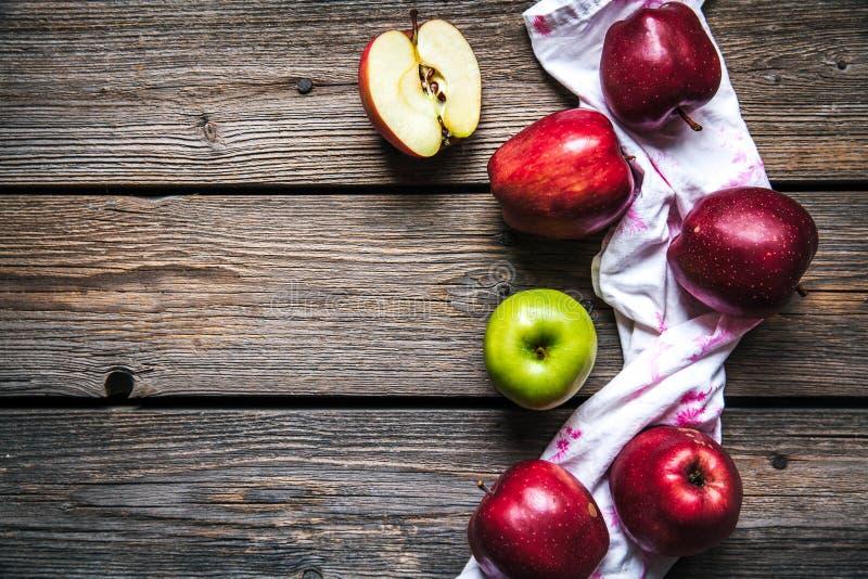 Rote Äpfel und ein Geschirrtuch auf hölzernem Hintergrund Frucht, Naturkost stockfotografie