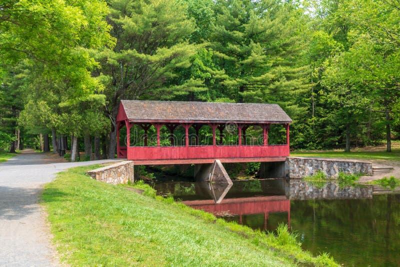 Rote überdachte Brücke nahe einem grünen Wald lizenzfreies stockbild