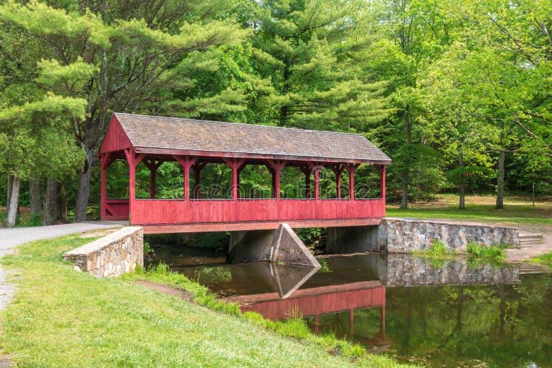 Rote überdachte Brücke nahe einem Wald stockbild
