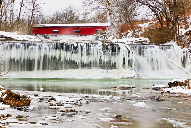 Rote überdachte Brücke und gefrorener Wasserfall lizenzfreies stockbild