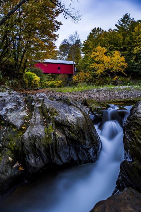 Rote überdachte Brücke und Wasserfall - Herbst/Fall - Vermont stockfotografie