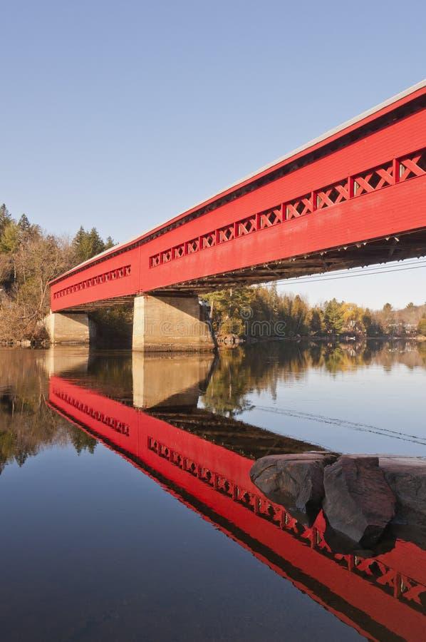 Rote abgedeckte Brücke mit Reflexion im Wasser stockfotografie
