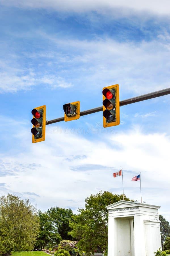 Rote Ampeln ?ber Kanada und USA-Flaggen auf Friedensbogen-Monument stockfotos