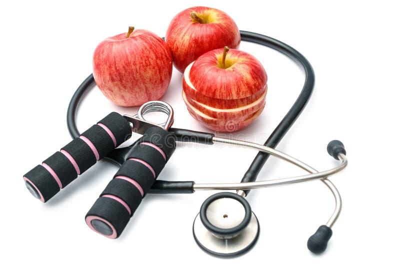 Rote Apfel- und Sportausrüstungen und Stethoskop, Diätplangesundheit lizenzfreie stockfotos