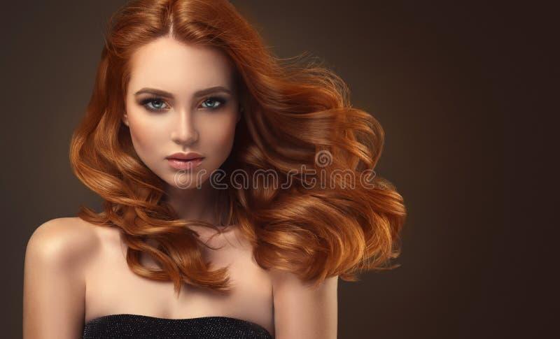 Rote behaarte Frau mit umfangreicher, glänzender und gelockter Frisur Attraktive junge Dame mit Kamm auf einem grauen Hintergrund lizenzfreie stockbilder