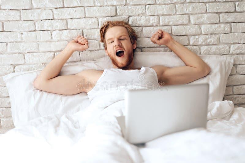 Rote behaarte junge Geschäftsmannausdehnungen im Bett stockbilder