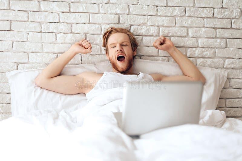 Rote behaarte junge Geschäftsmannausdehnungen im Bett lizenzfreies stockbild