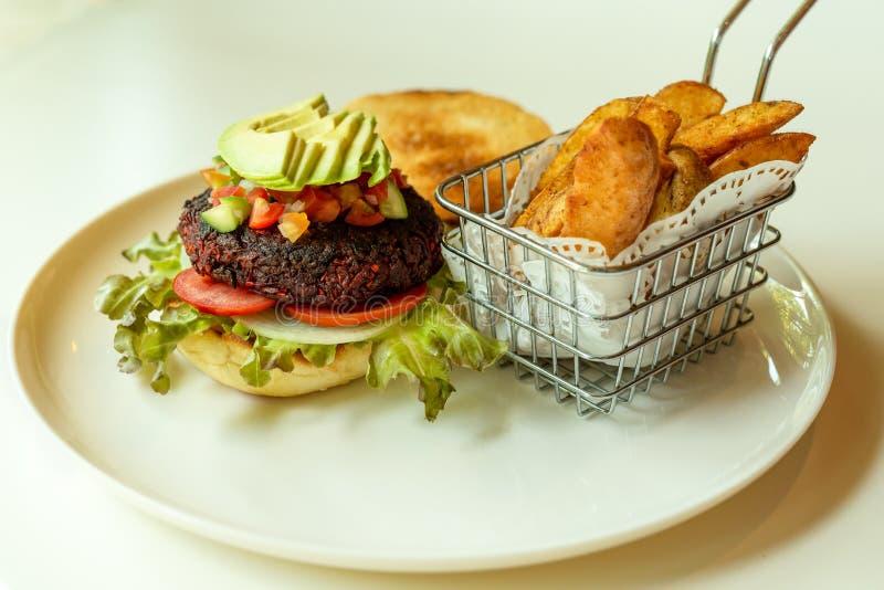 Rote-Bete-Wurzeln Burger mit Salat in einem krustigen Brötchen und in den Chips lizenzfreie stockbilder