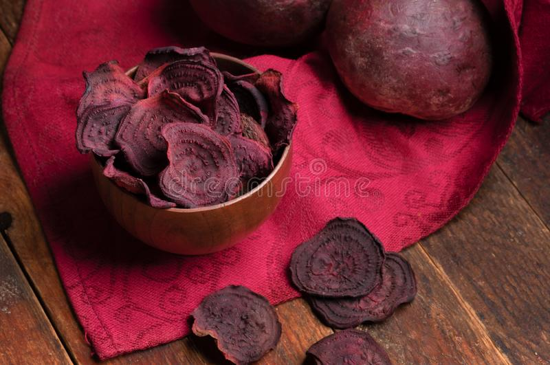 Rote-Bete-Wurzeln Chips in der hölzernen Schüssel und in den ganzen Rote-Bete-Wurzeln auf roter Serviette auf altem Holztisch stockfotos