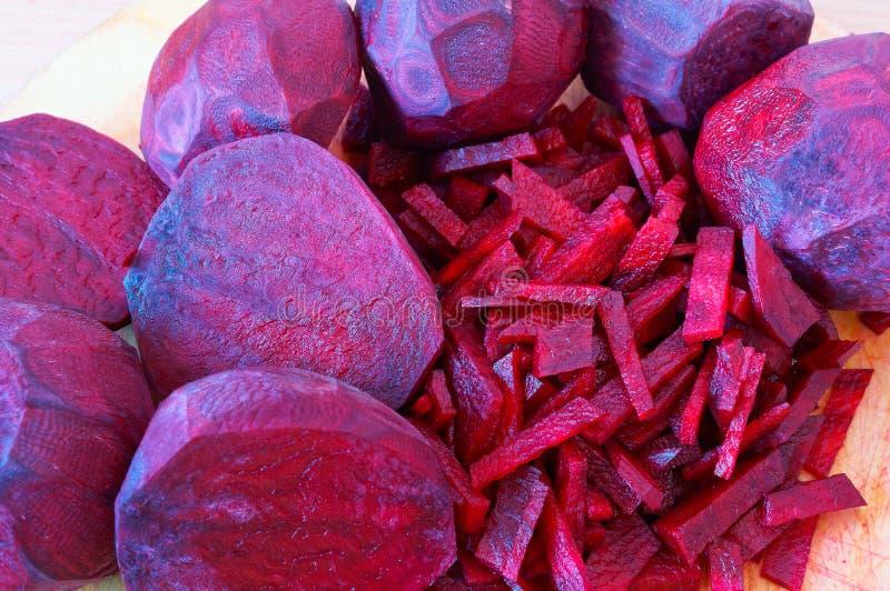 Rote-Bete-Wurzeln geschnittene Streifen, rote Rübe hackten Hälften, rohe Rote-Bete-Wurzeln für das Kochen stockfotografie