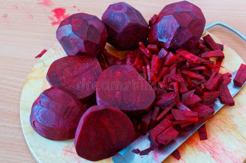 Rote-Bete-Wurzeln geschnittene Streifen, rote Rübe hackten Hälften, rohe Rote-Bete-Wurzeln für das Kochen lizenzfreie stockfotografie