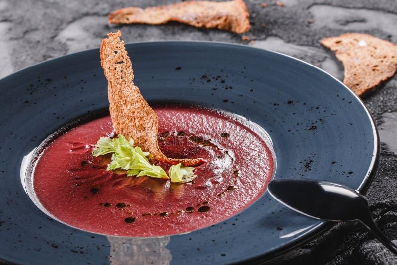 Rote-Bete-Wurzeln Sahnesuppe mit Sellerie und Croutons in der Platte auf dunkelgrauem Hintergrund mit L?ffel und Serviette Gesund stockfotos