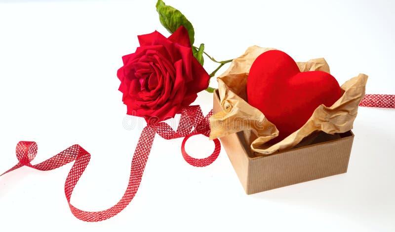 Rote Blume Rose mit Grün lässt Stamm und Mitbringsel mit Band und Herz auf weißem Hintergrund stockbild