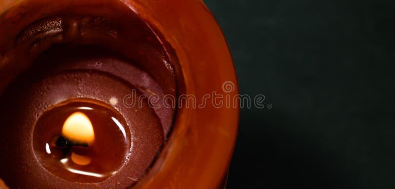 Rote brennende Kerze auf einem dunklen Hintergrund lizenzfreie stockfotografie