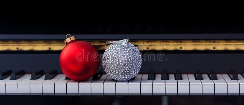 Rote Chritmas-Bälle auf Klaviertastatur, Vorderansicht lizenzfreie stockfotografie