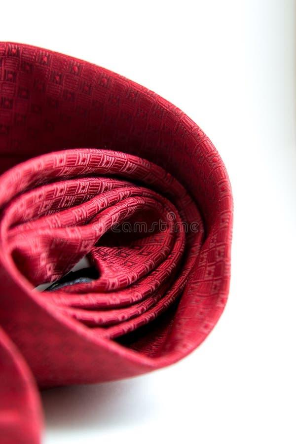 Rote Designkrawatte gerollt mit weißem Hintergrund lizenzfreies stockfoto