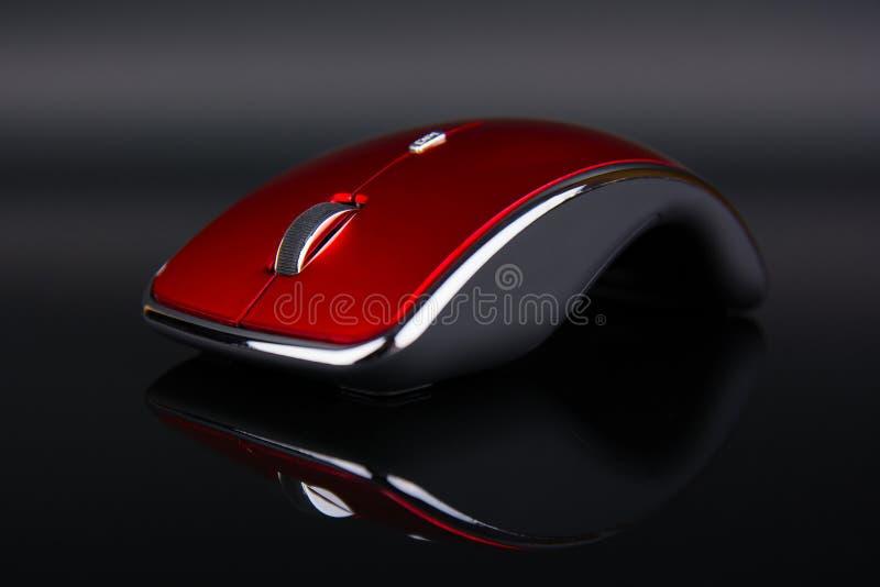 Rote drahtlose Maus auf dunklem reflektierendem Hintergrund stockfoto