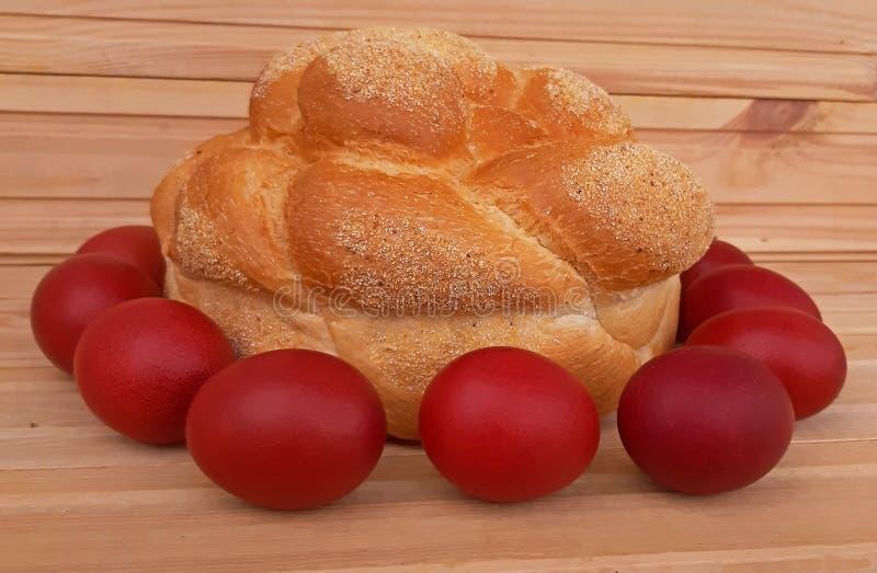 Rote Eier Ostern und selbst gemachtes Brot Junges K?ken in Wanne, 2 malte Eier und Blumen stockfoto