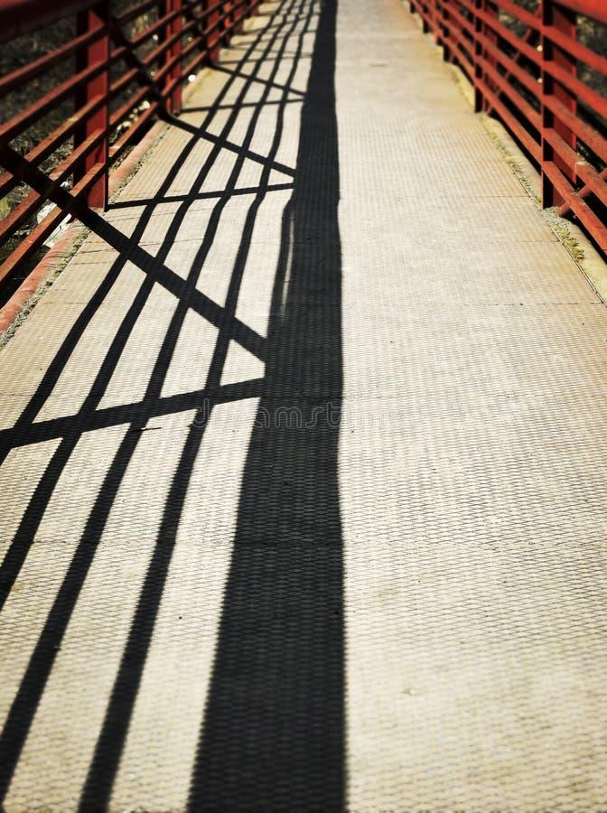 Rote Eisenbrücke mit Schatten lizenzfreies stockfoto
