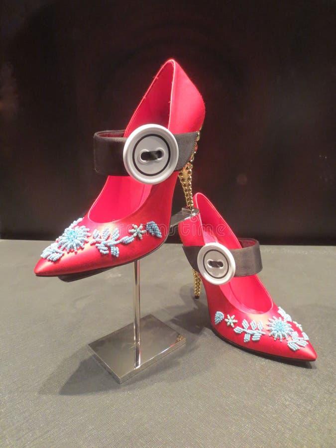 Rote elegante moderne Schuhe mit einem schwarzen Bügel in einem Shopfenster stockbild