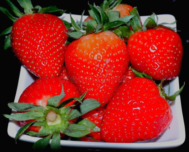 Rote Erdbeere auf einer weißen quadratischen Untertasse lizenzfreies stockfoto