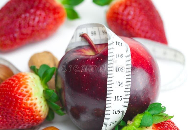 Rote Erdbeeren, Blume, Apfel und Maßband lizenzfreies stockfoto