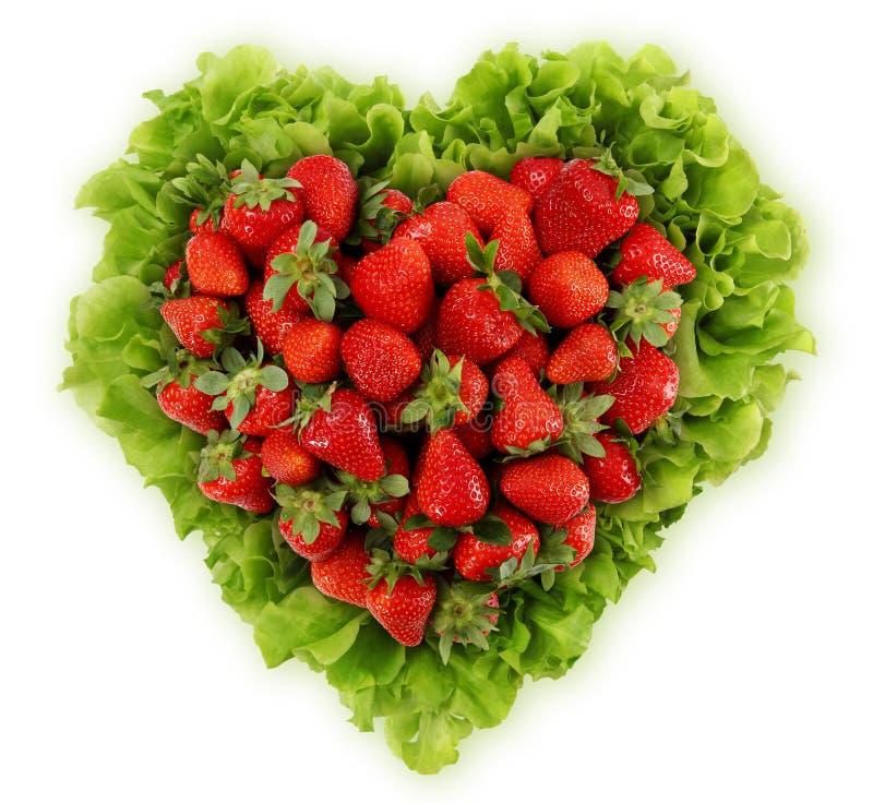 Rote Erdbeeren im Herzen formen mit dem Salat, der auf weißem Hintergrund lokalisiert wird stockfotografie