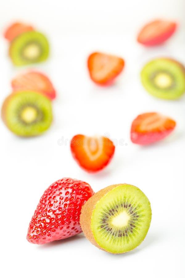 Rote Erdbeeren und grüner Kiwischnitt in die Hälfte vereinbart auf einem weißen Hintergrund lizenzfreies stockfoto