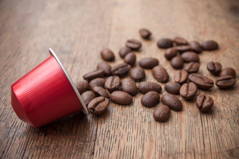 rote Espressokaffeekapsel mit Kaffeebohnen auf Holz lizenzfreies stockfoto