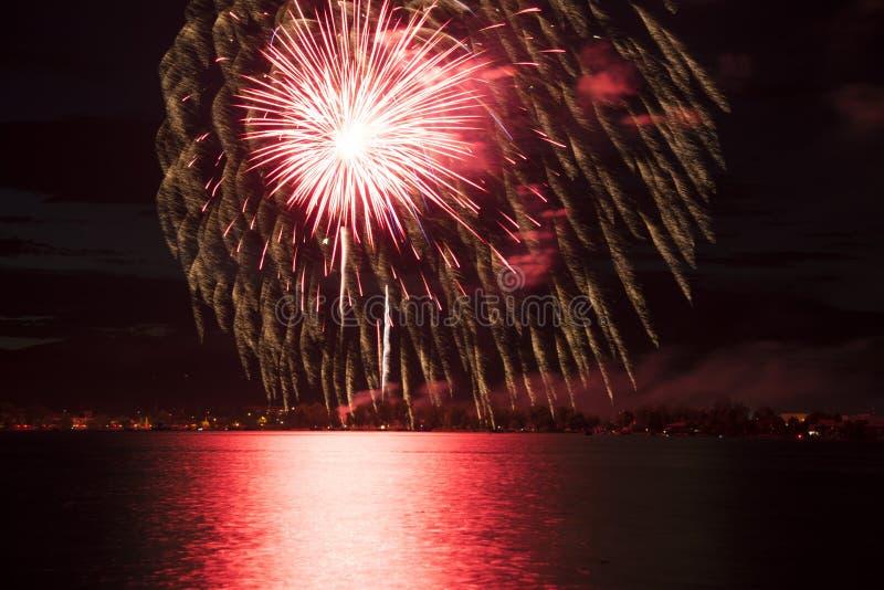 Rote Feuerwerke, die über See sich reflektieren stockbild