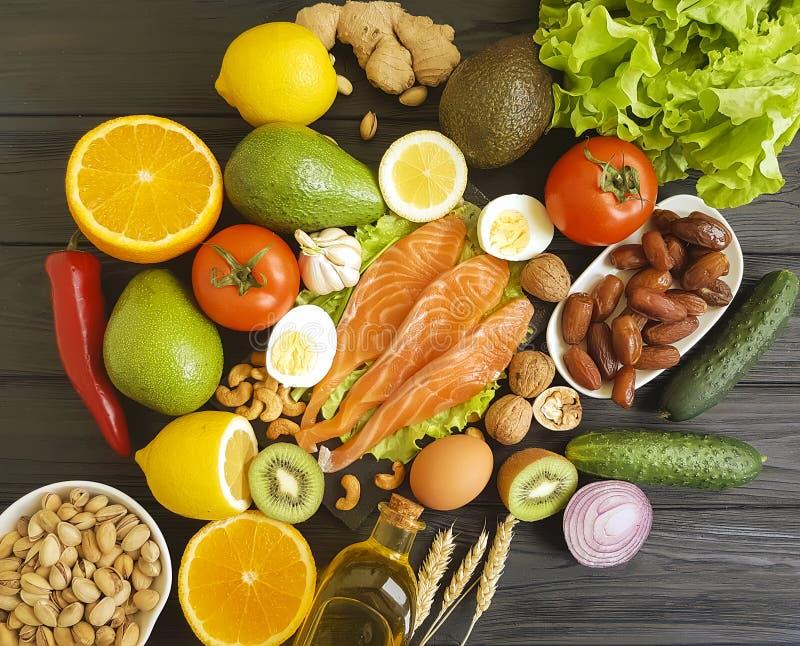 rote Fische, Avocado, Nüsse auf einem schwarzen hölzernen Hintergrund, gesundes Lebensmittel stockfoto