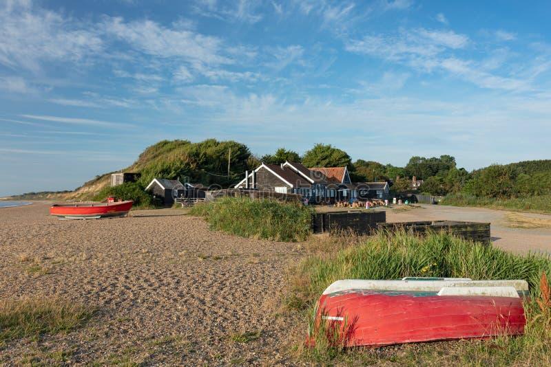 Rote Fischerboote auf dem Schindelstrand bei Dunwich, Suffolk, England lizenzfreie stockbilder