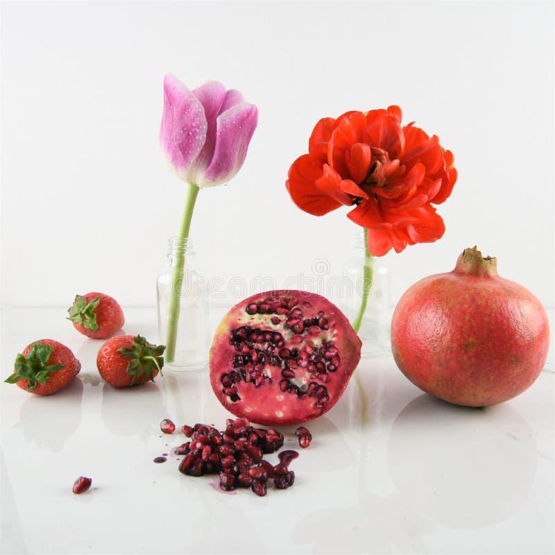 Rote Früchte und Tulpen auf weißem Hintergrund stockfotos