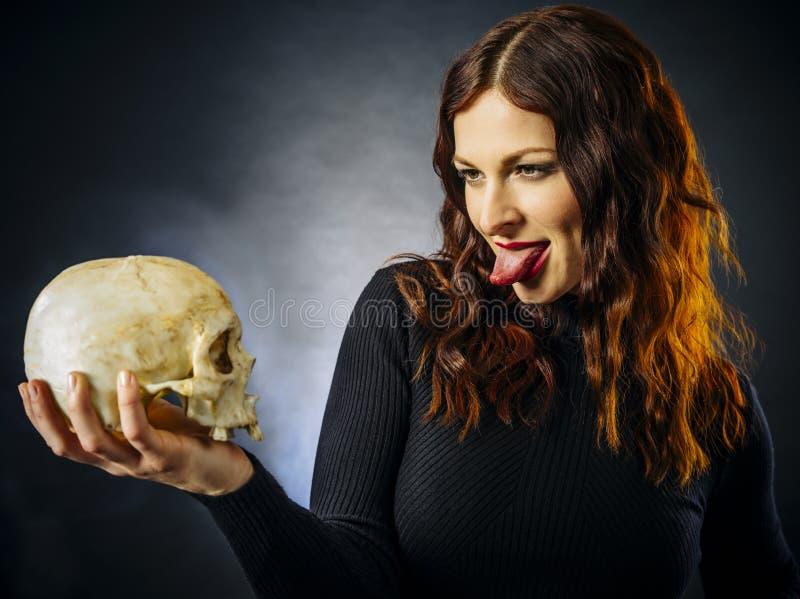 Rote Frau, die sich die Zunge am Schädel ausstreckt stockfotografie