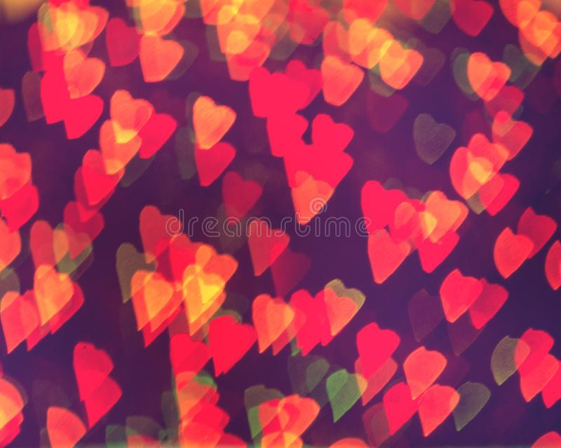Rote Funkelnweinlese beleuchtet Hintergrund mit kleinen Herzen lizenzfreie stockbilder