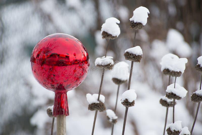 Rote Gartenkugel im Schnee stockbild