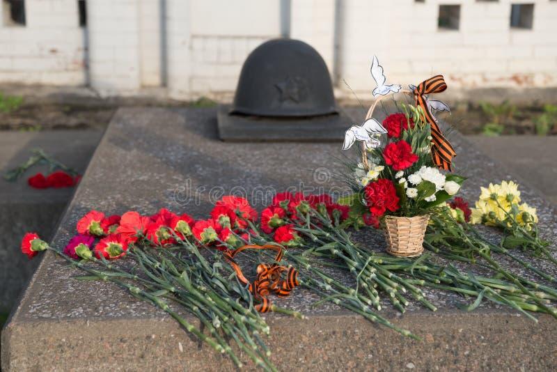 Rote Gartennelkenblumen werden auf den Grabstein Victory Memorials während der Feier von Victory Day gelegt lizenzfreie stockfotografie