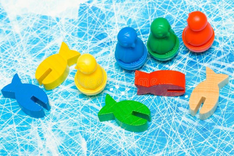 rote, gelbe, blaue, grüne Fische und Pinguinholzspanzahl im Kinderspiel - Brettspiel und Kinderfreizeitkonzept stockbilder