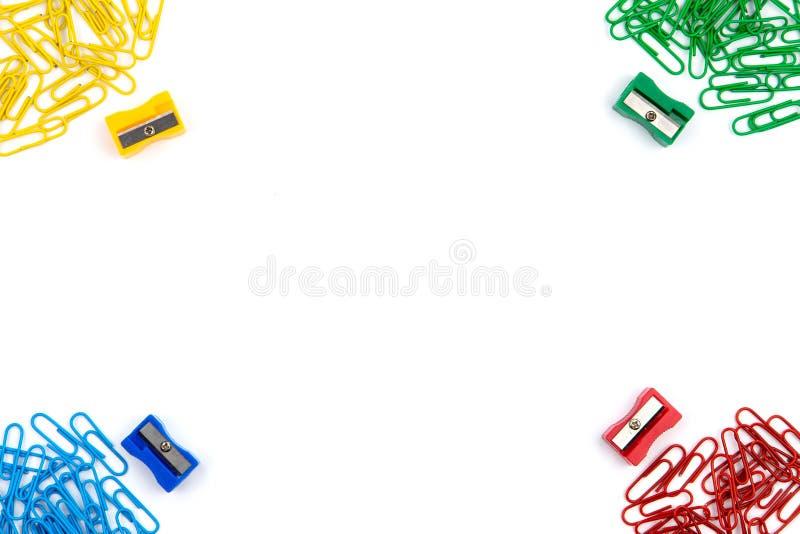 Rote, gelbe, blaue und grüne Briefpapierclip und Bleistiftspitzer liegen in den verschiedenen Winkeln des Blattes auf einem weiße lizenzfreie stockfotografie